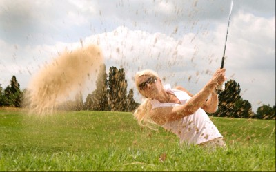 girl golfing in sand trap