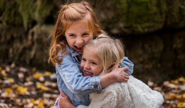 two little girls hugging and laughing