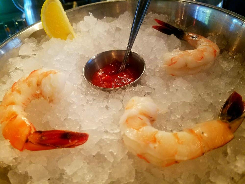 shrimp on ice in a stainless steel bopwl with a small container of cocktail sauce in the middle