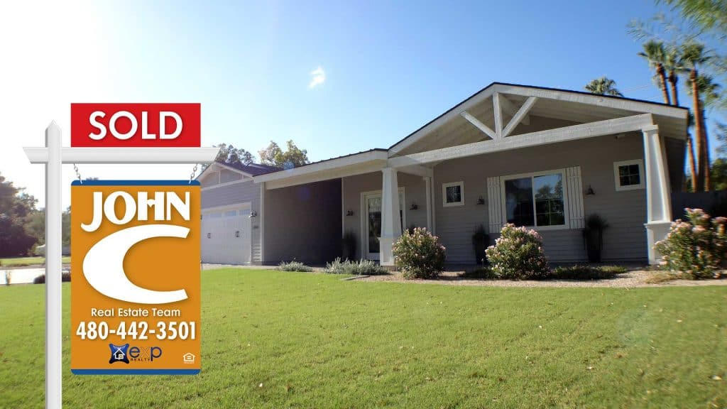 Phoenix Home with a John Cunningham eXp realty SOLD sigjn in the front yard