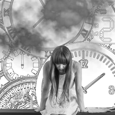woman on bench with head down and large clocks in the background