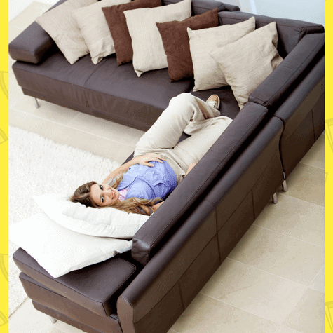 Modern leather couch with pregnant woman laying down who is probably thinking about selling her house LOL