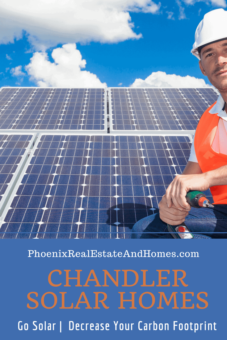 A professional young solar panel installer is sitting on the roof where he recently installed panels on Chandler Solar Homes.